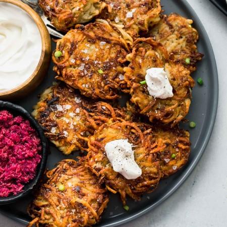 POTATO LATKES ON GREY PLATE TOPPED WITH DOLLOPS OF SOUR CREAM AND SERVED WITH BOWL OF PINK BEET HORSERADISH SAUCE.