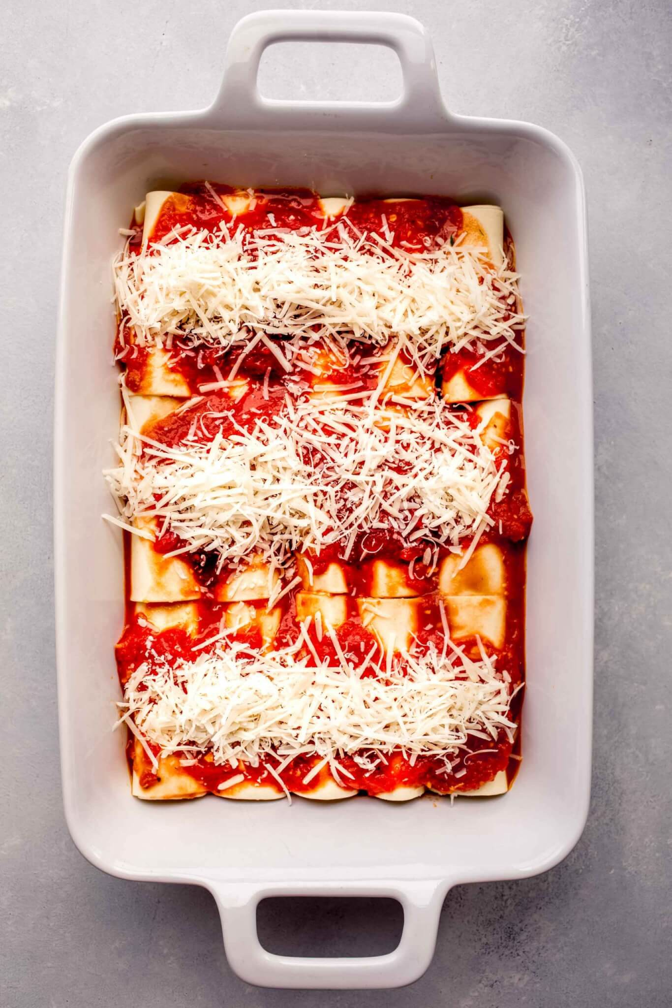 Unbaked manicotti arranged in baking dish.