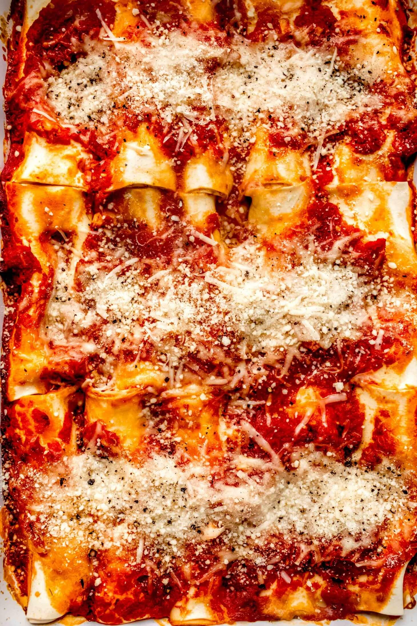 Baked manicotti topped with melted cheese, arranged in baking dish.