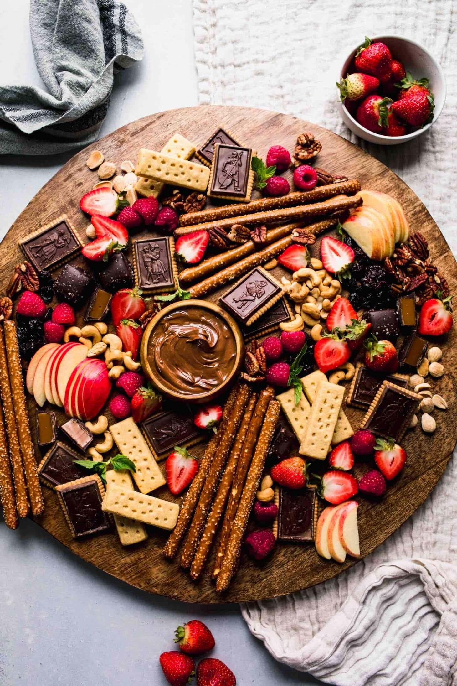 Dessert board arranged on wood round serving tray.