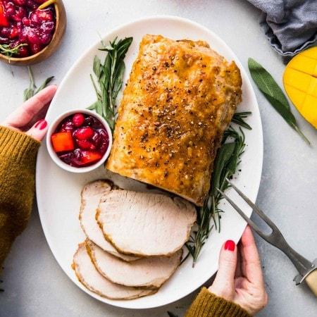 Hands holding platter of glazed pork loin next to mango cranberry sauce and fresh herbs.