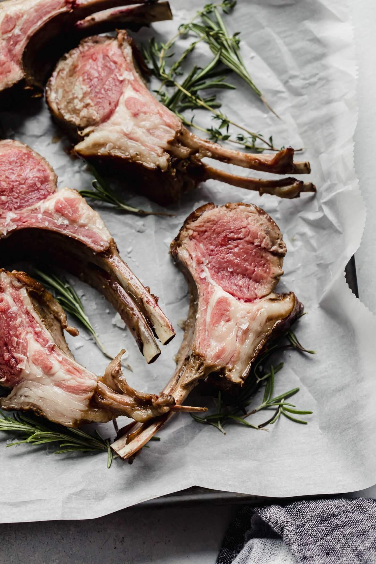 Rack of lamb sliced into chops and laid out on tray next to fresh herbs.