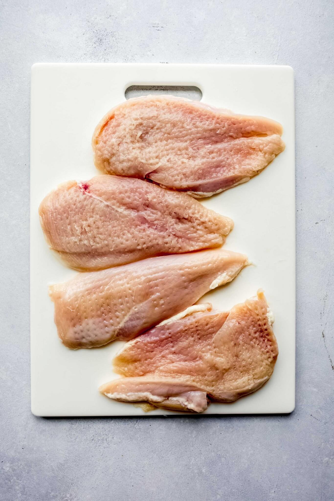 Chicken cutlets on cutting board.