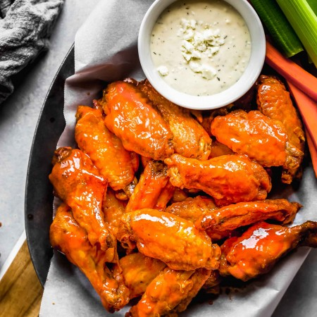 Air fryer wings in serving basket with blue cheese and celery sticks.