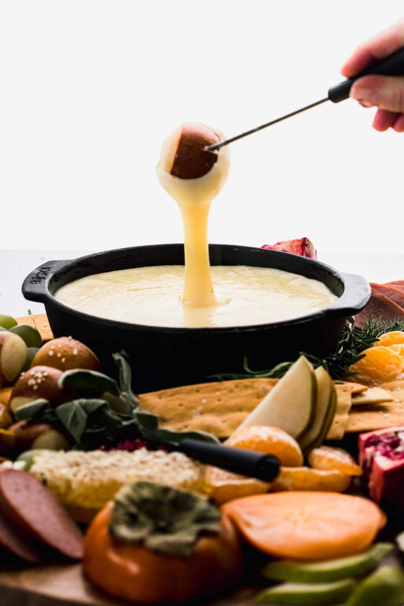 Pretzel bite being dipped into fondue.