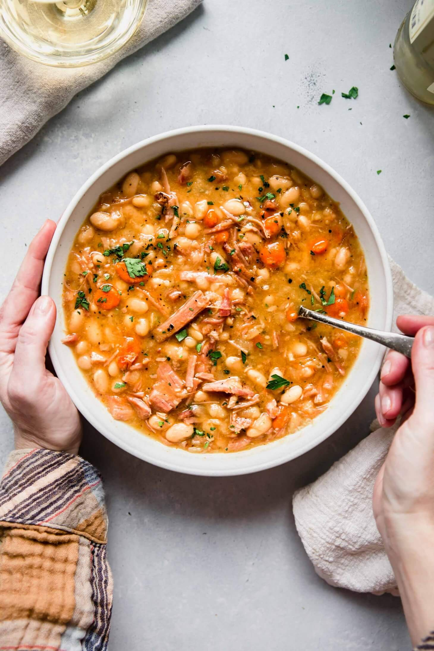 Bowl of Slow Cooker Ham and Bean Soup with hands holding bowl and spoon