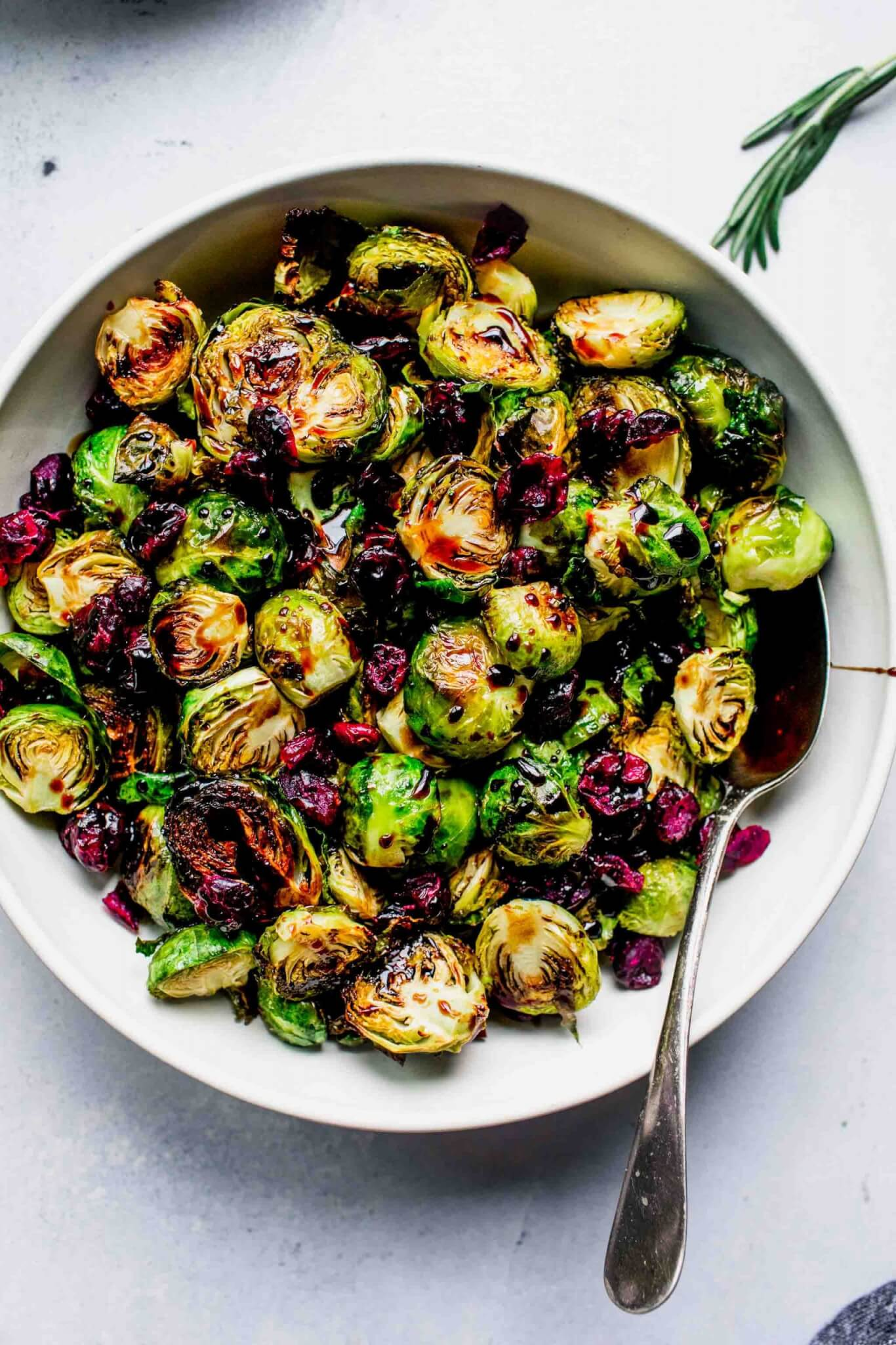 Roasted sprouts in bowl drizzled with balsamic glaze and sprinkled with cranberries.