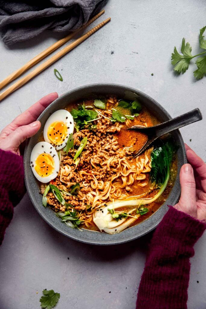Bowl of dan dan noodles topped with bok choy, green onions and a soft boiled egg.
