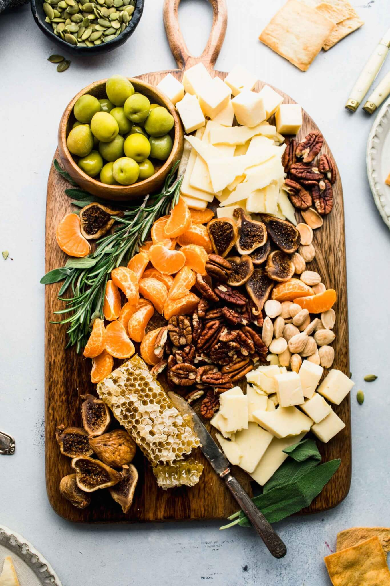 Cheeses, nuts, olives and fruits arranged on wooden serving board.