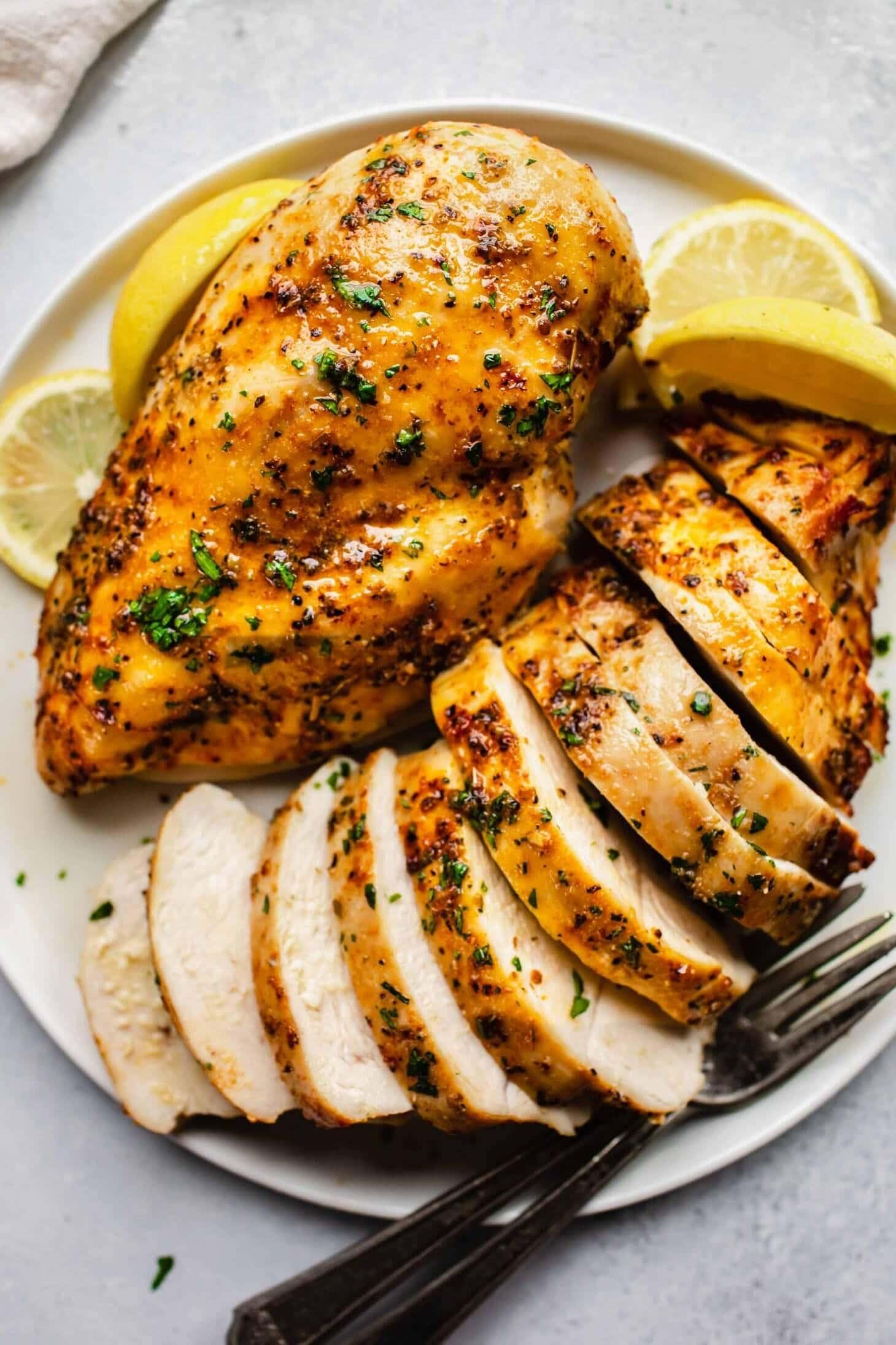 Sliced chicken breast on white plate.