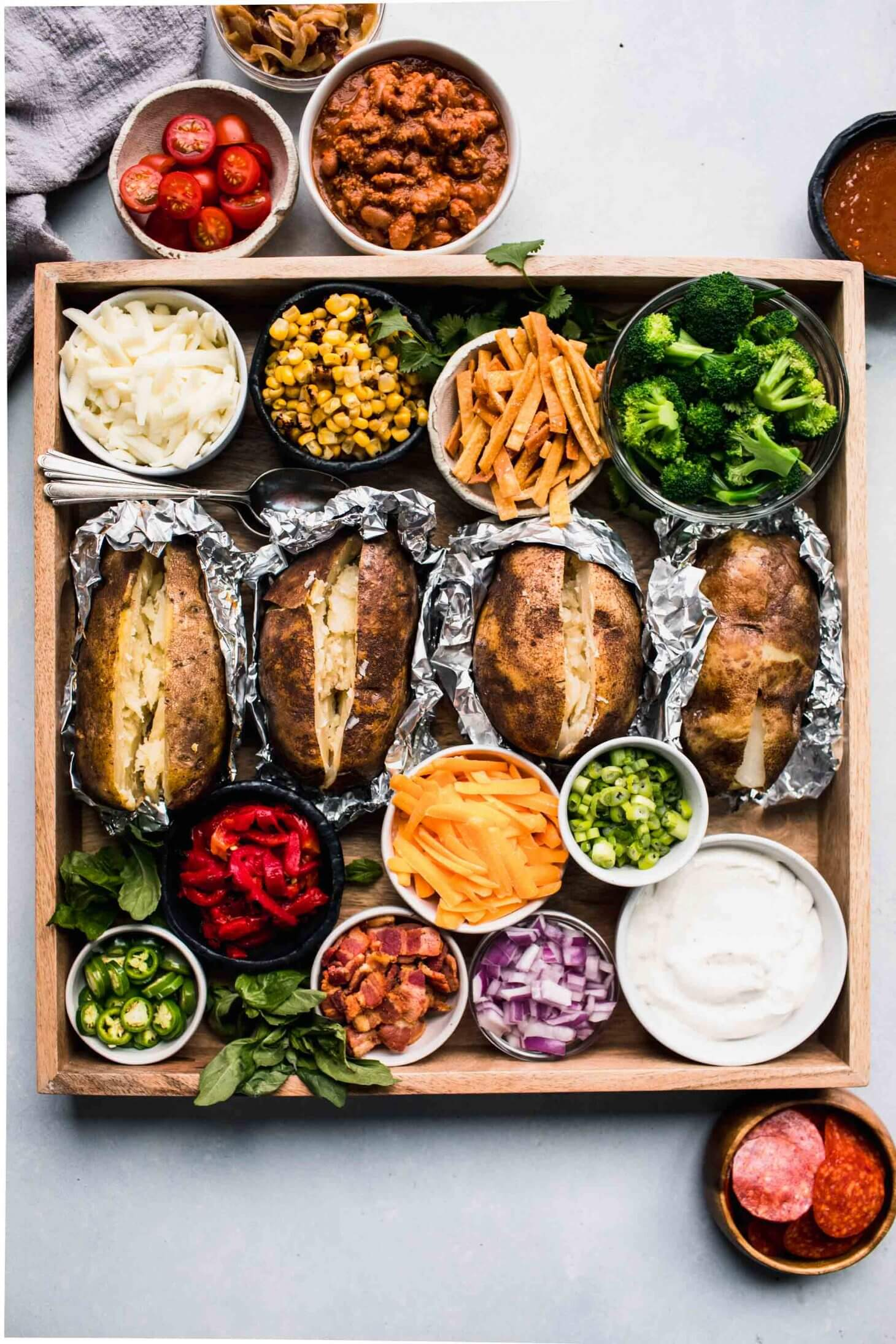 Baked potatoes on wooden tray surround with toppings.