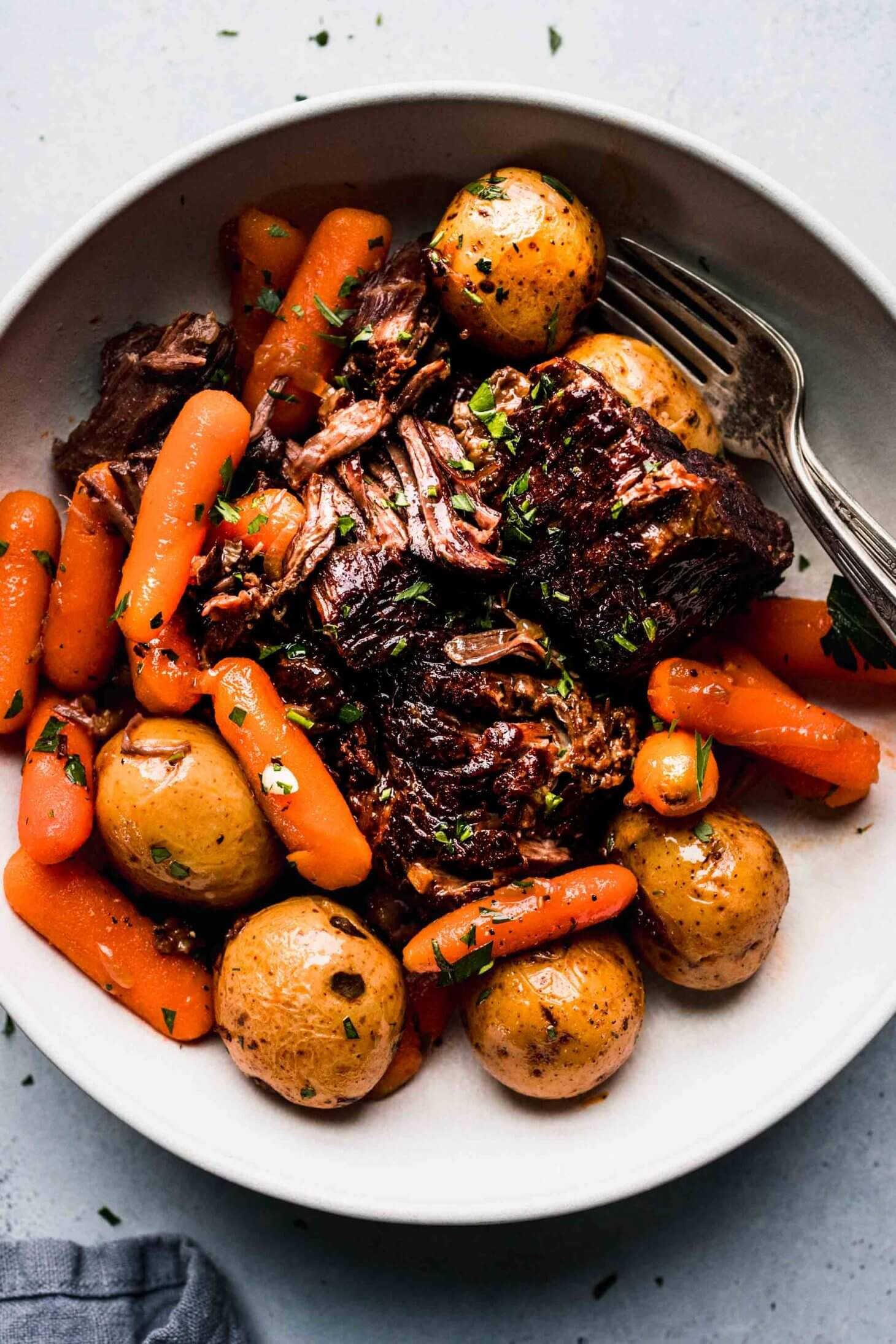 Pot roast, potatoes and carrots arranged in white bowl.