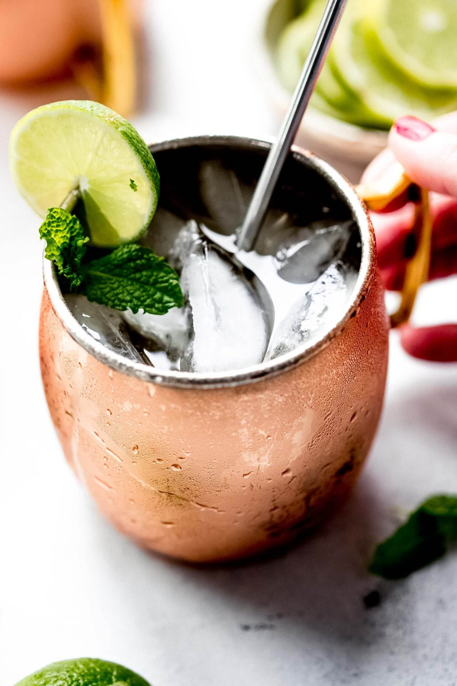 Moscow mule in copper mug with hand holding handle