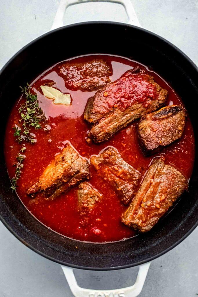 top shot of meat cooking in red sauce in dutch oven