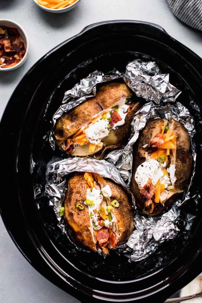 Baked potatoes in crockpot topped with toppings.