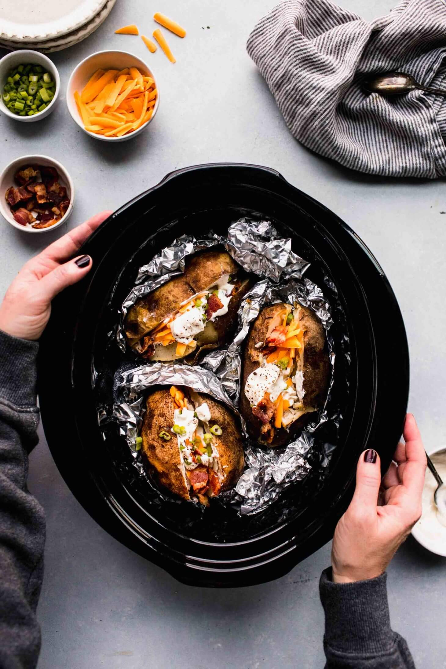 Hands holding slow cooker filled with baked potatoes in foil topped with toppings.
