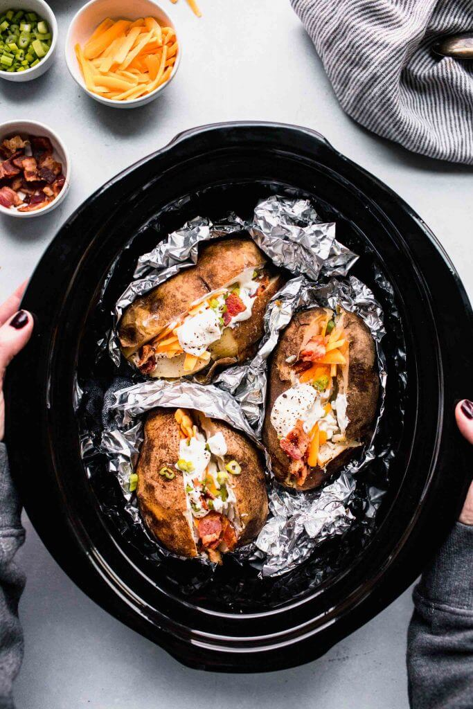 Hand holding slow cooker filled with potatoes.