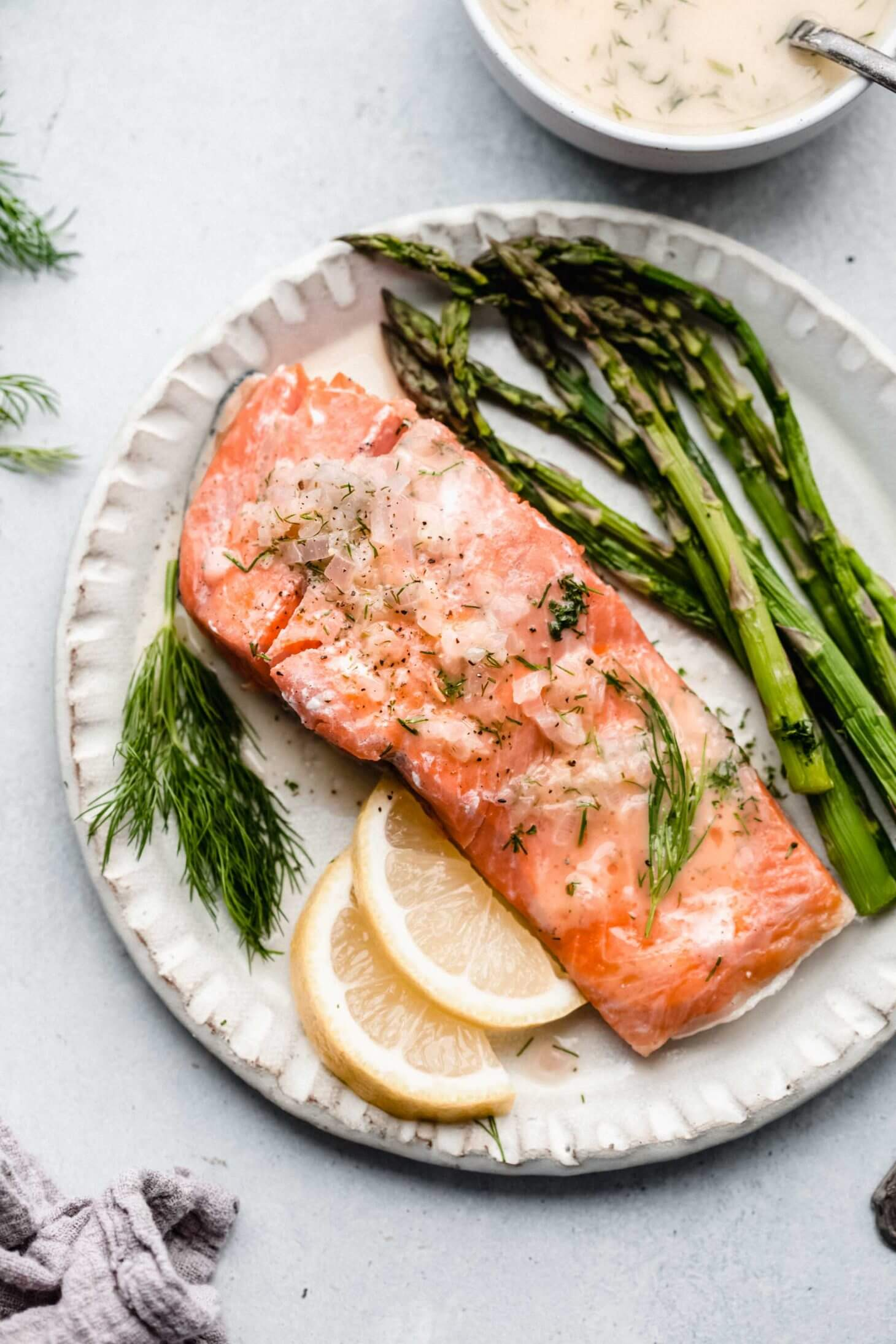 salmon with asparagus and lime wedges on white plate