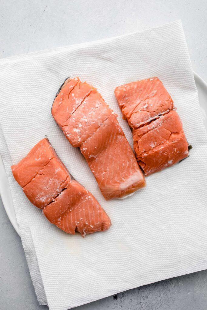 salmon filets seasoned with salt on paper towel