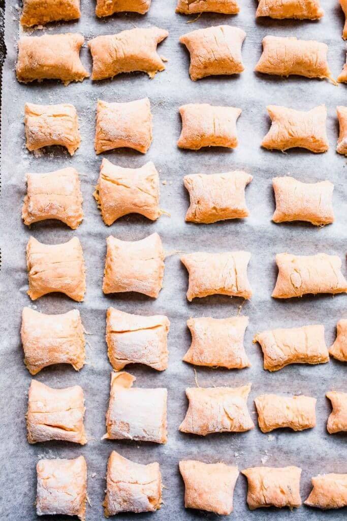 Formed sweet potato gnocchi on baking sheet.