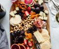 Cheeses, crackers and fruits and nuts on wood serving tray next to glass of wine.