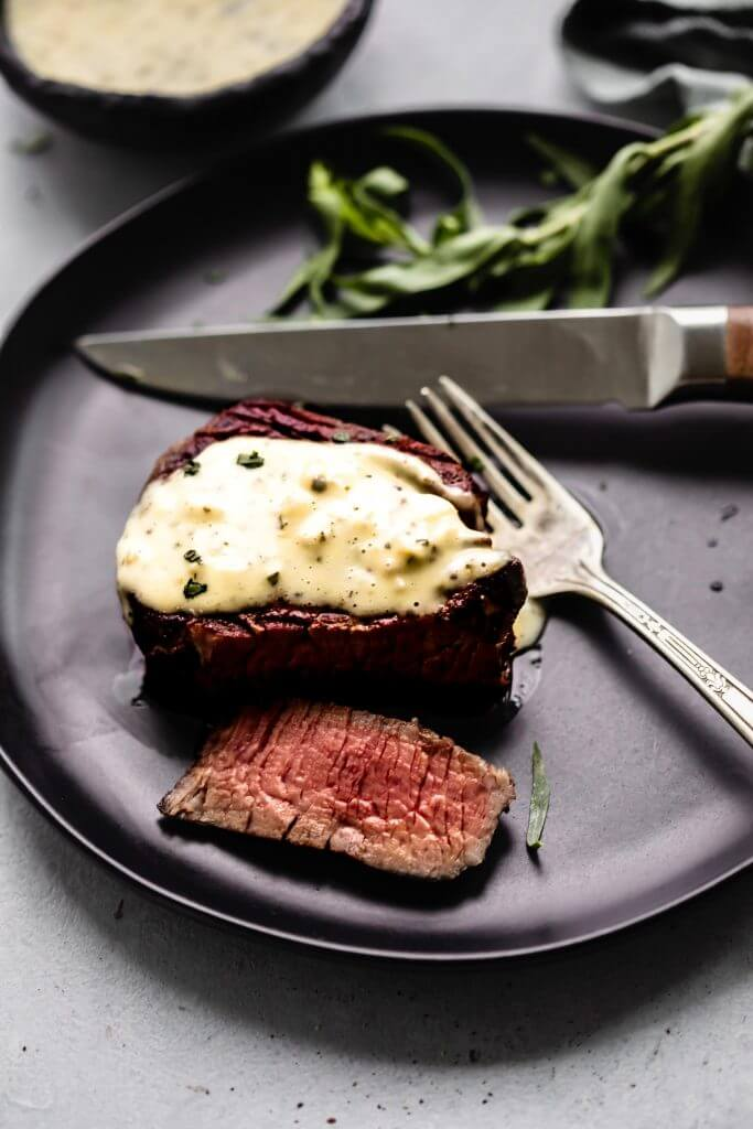Steak with bearnaise sauce drizzled on top, on a black plate with fork and knife