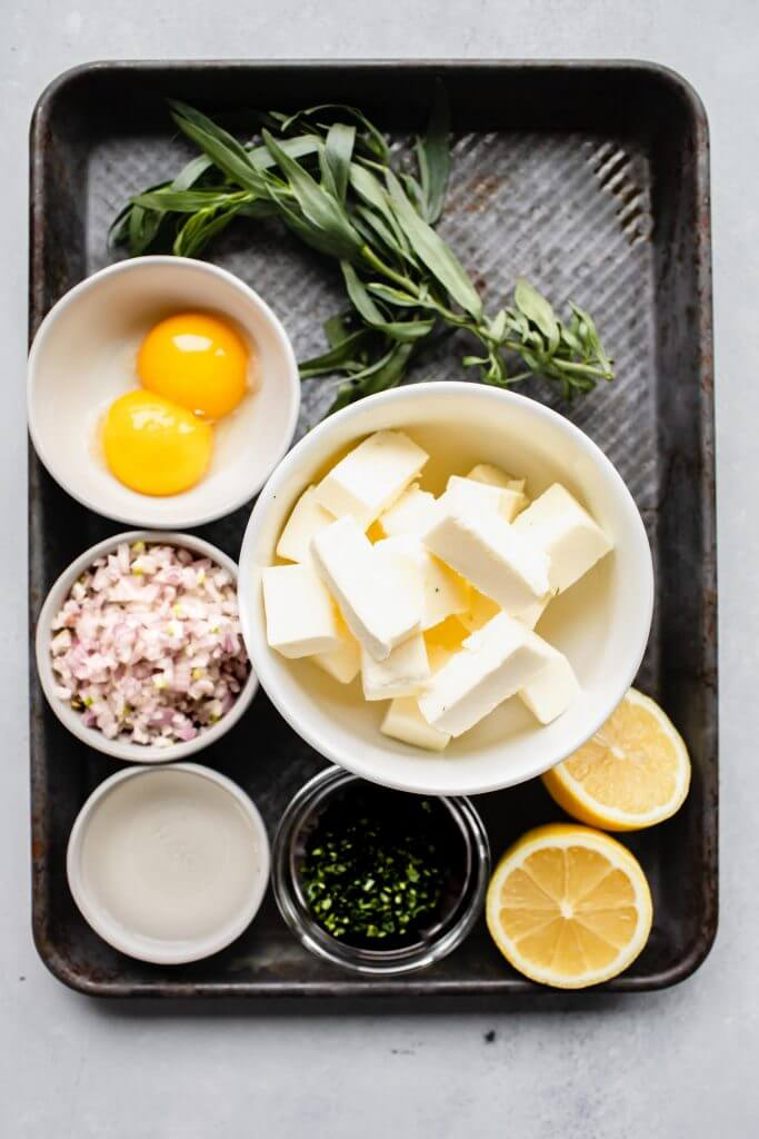 Black tray fill of ingredients: egg yolks, unsalted butter, tarragon leaves, lemon, minched shallot, and white wine vinegar