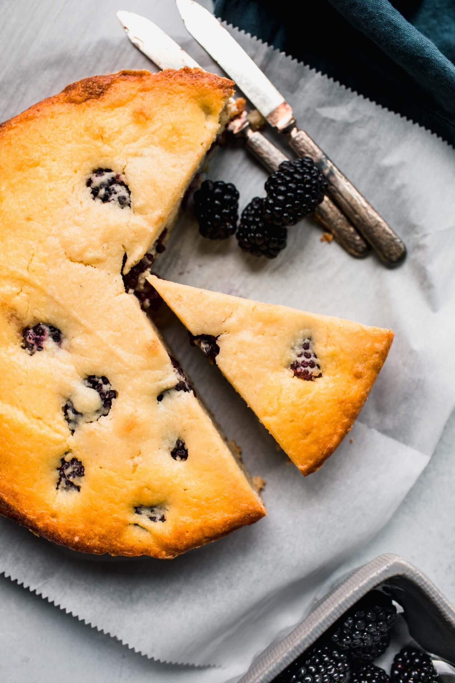 Ricotta cake cut into pieces next to blackberries.