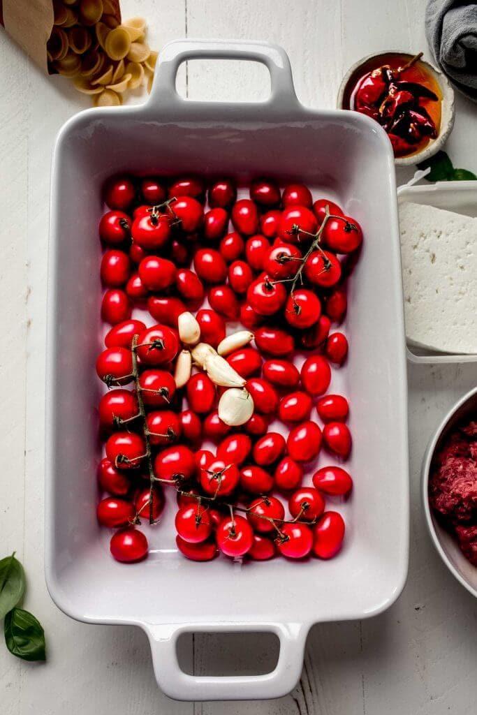 Cherry tomatoes and garlic in baking dish.