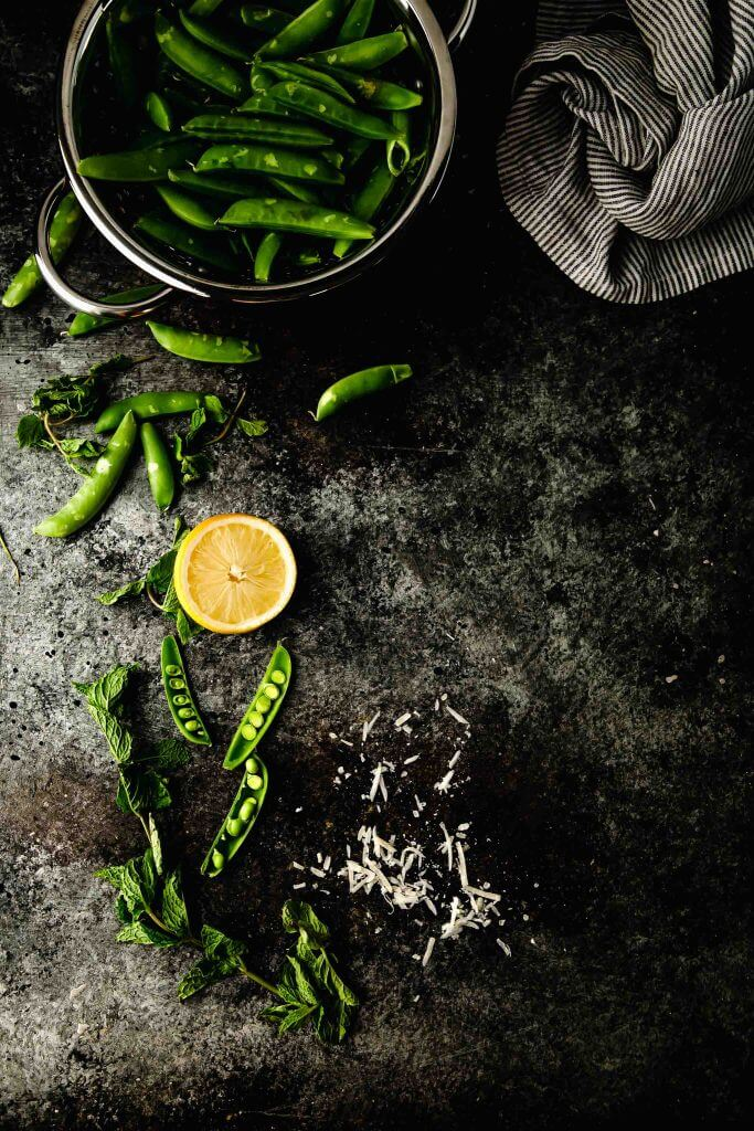 Peas, parmesan and lemon on dark grey counter.