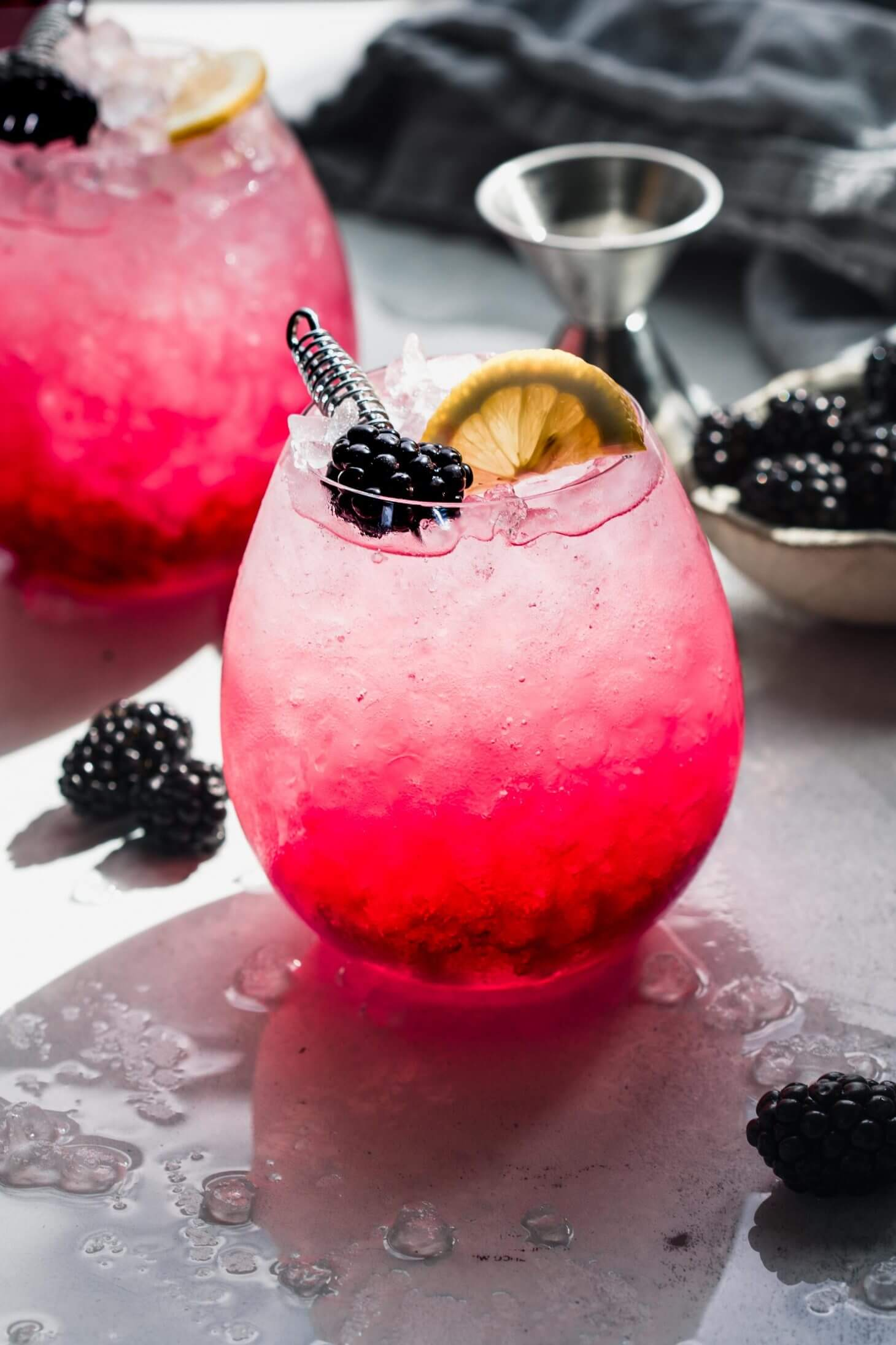 Side view of bramble cocktail garnished with lemon and blackberry.