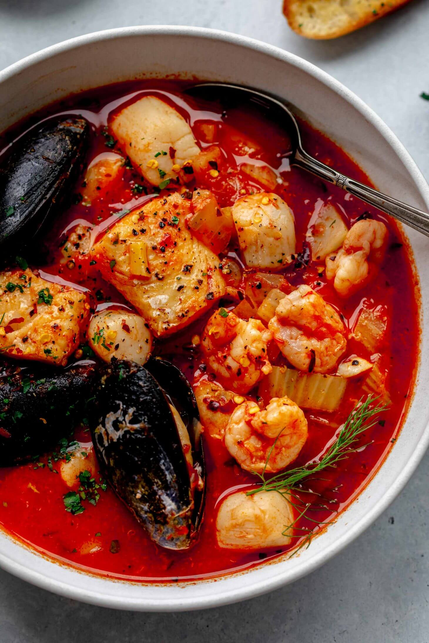 Overhead shot of cioppino in white bowl with spoon.