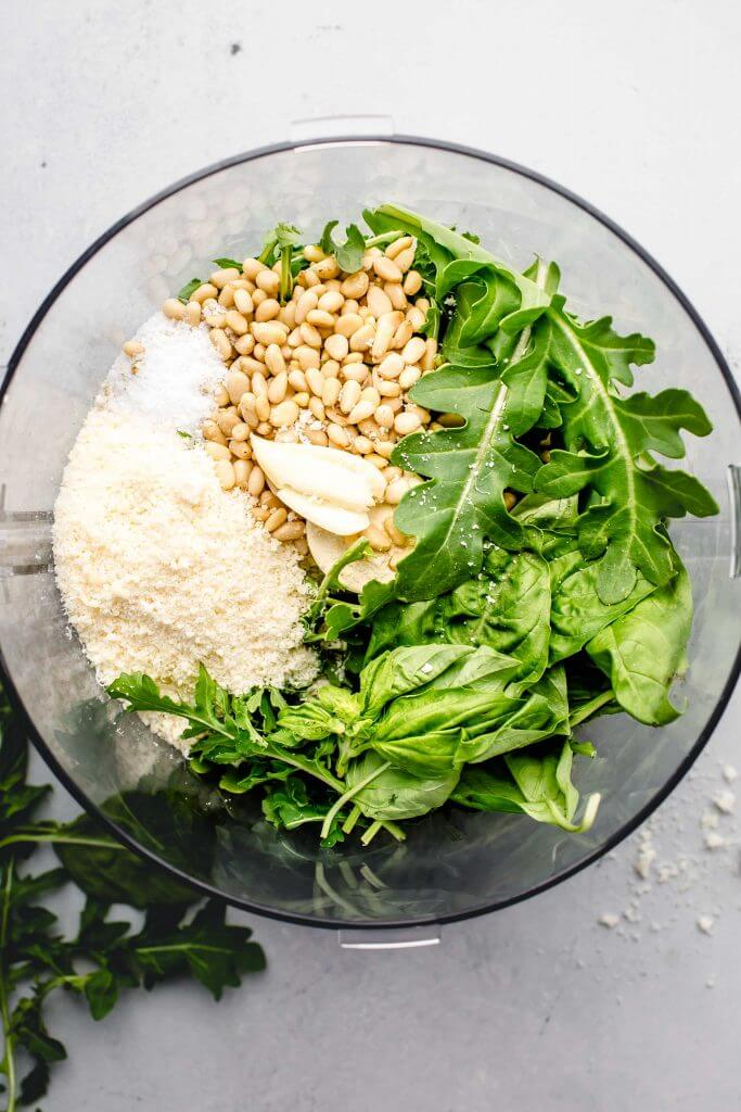 Ingredients for arugula pesto in food processor.