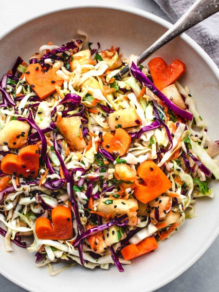 Prepared hawaiian slaw in bowl with heart shaped carrots.