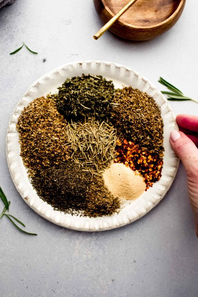 Hand holding plate of spices.