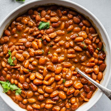Bowl of cooked pinto beans flecked with cilantro.