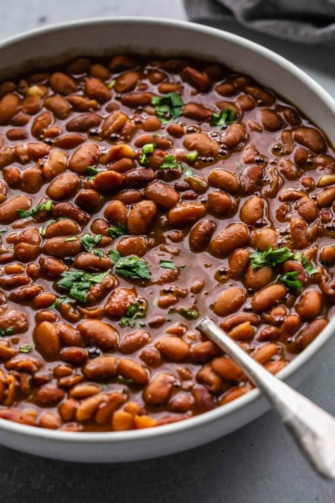 side view of bowl of cooked pinto beans.