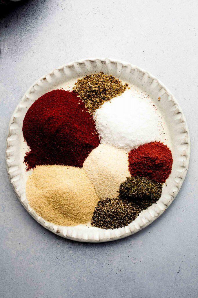Scoops of ingredients for cajun seasoning on plate.