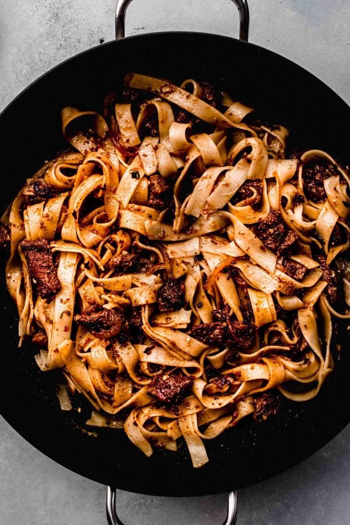 Cumin lamb noodles in wok.