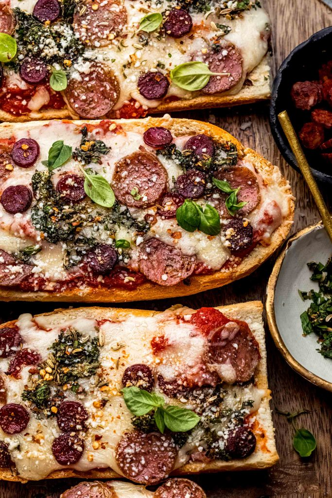 French bread pizza slices on cutting board next to small bowl of herbs and pepperoni.