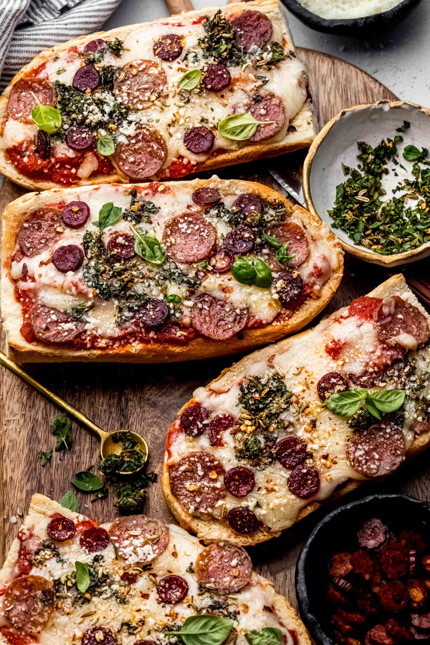 French bread pizzas on cutting board next to small bowl of herbs and pepperoni.